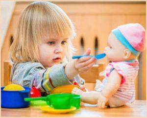 Девочка кормит куклу