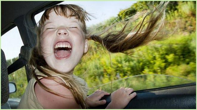 Девочке на фото весело в поездке
