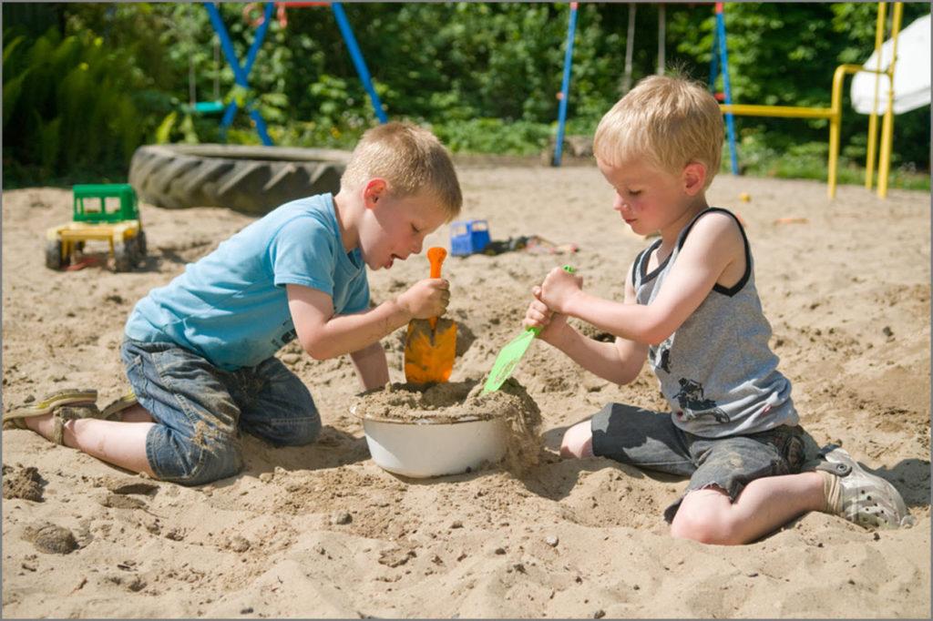Мальчишки что-то строят из песка