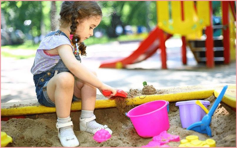 Девочка с косичками в песочнице