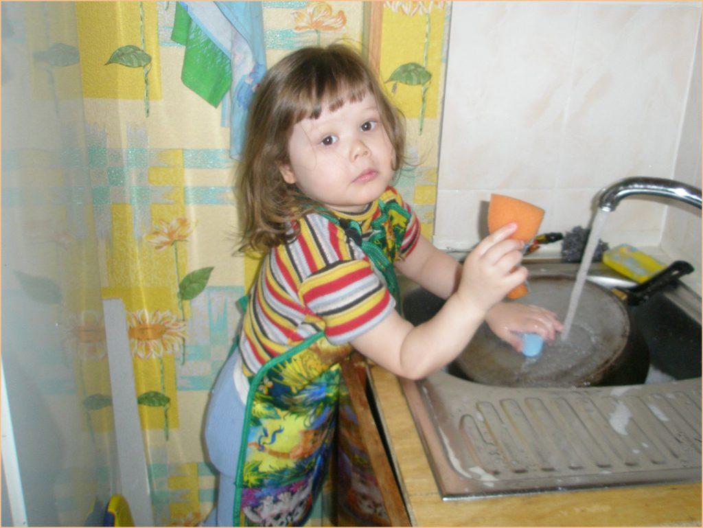Девочка на фото моет посуду