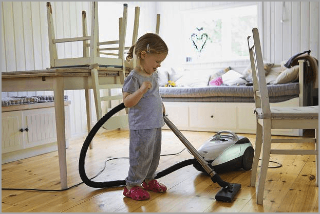 Девочка пылесосит полы в детской комнате