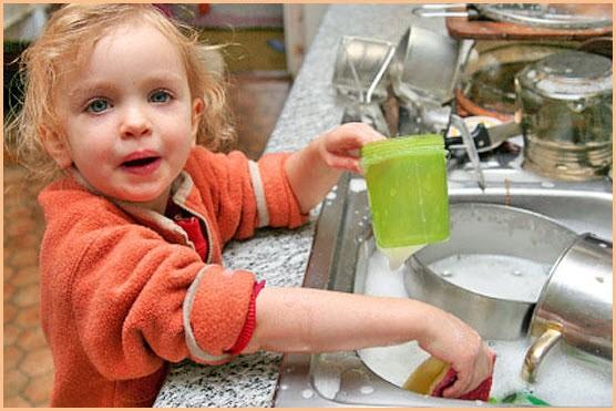 Маленькая помощница моет посуду в раковине