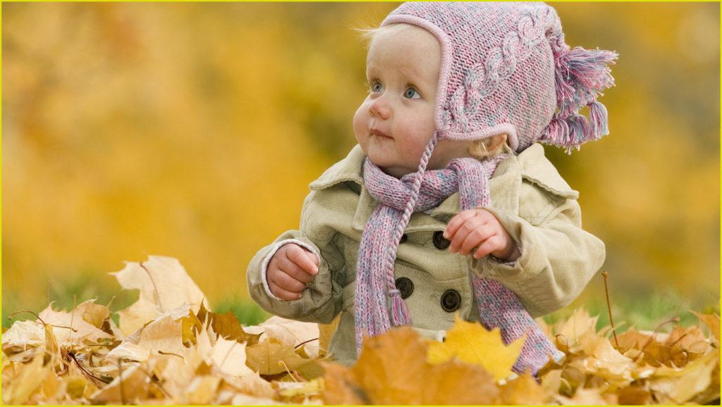Ребёнок как куклёнок среди осенних листьев