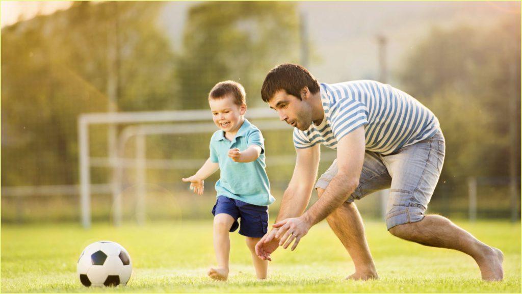 Мальчуган с папой играют в футбол