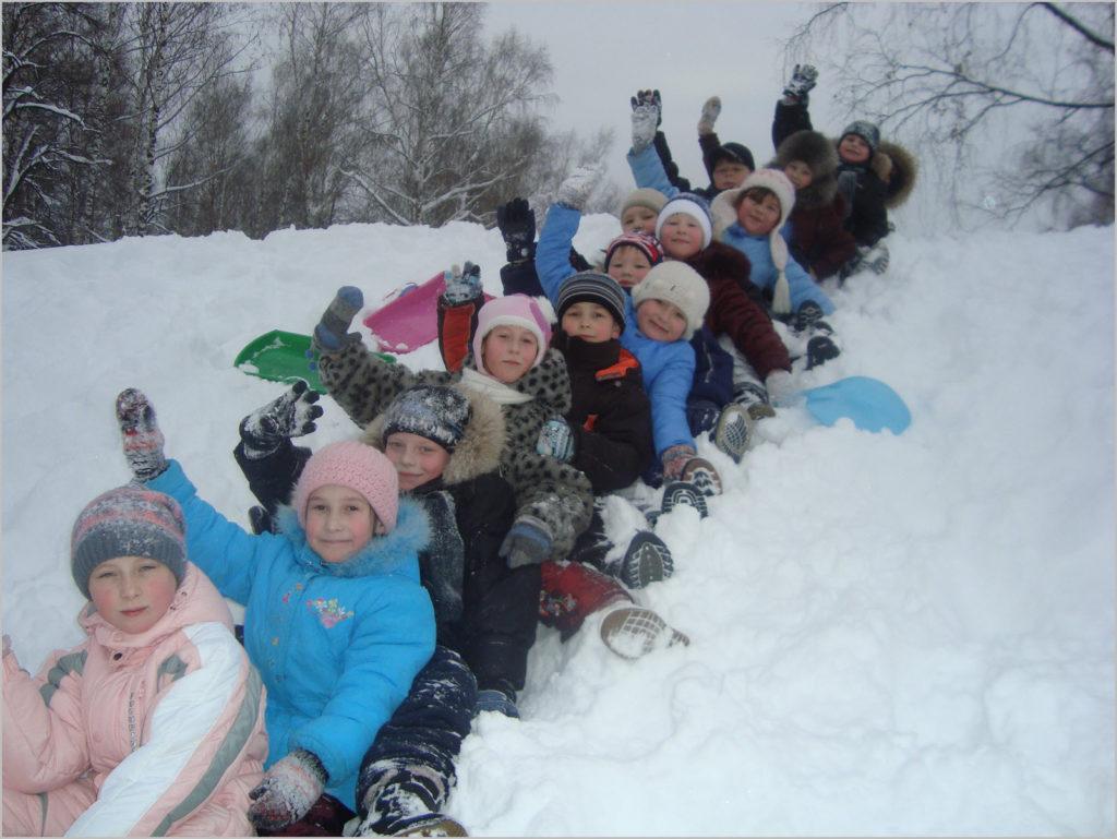 Дети катаются с горы паровозиком