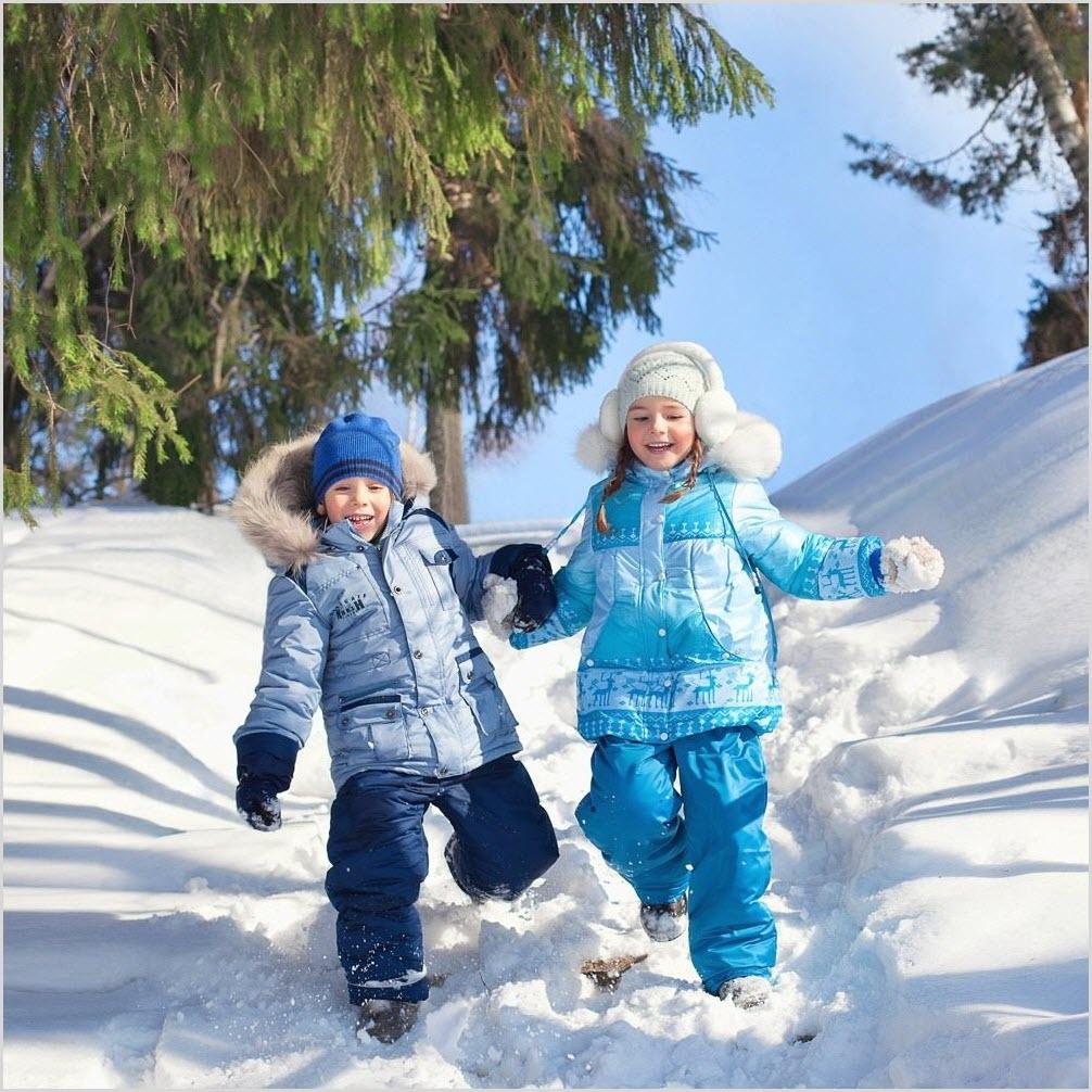 Мальчик с девочкой бегут по снегу с горы