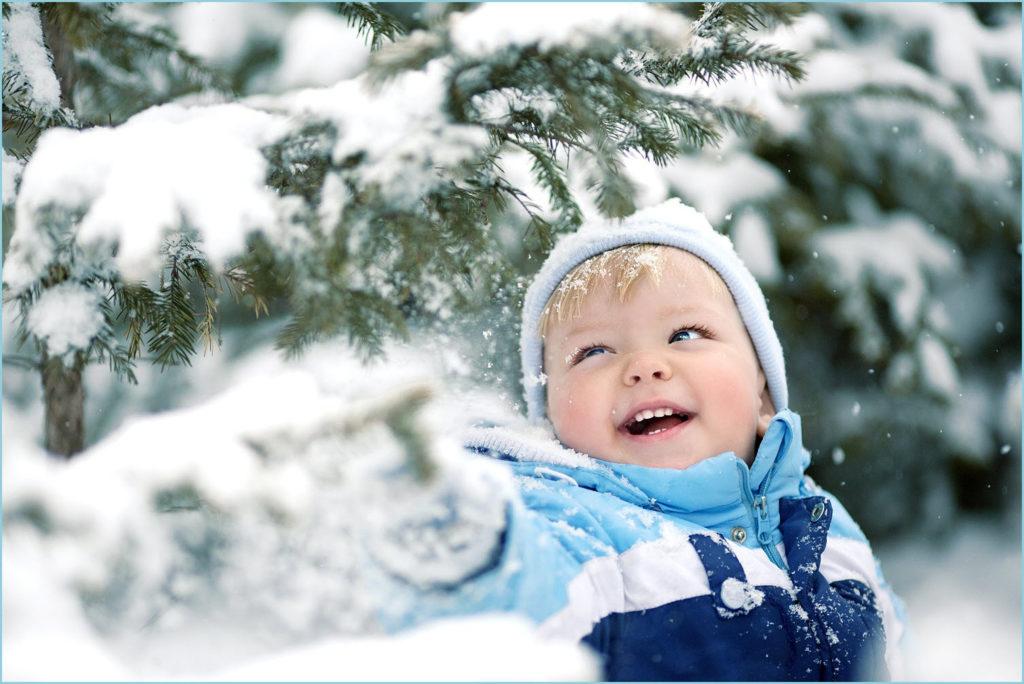 Мальчуган стряхивает снег с веток ели