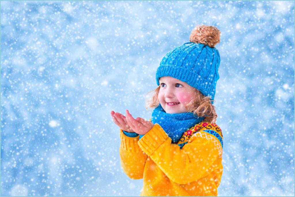 Девочка ловит руками снежинки