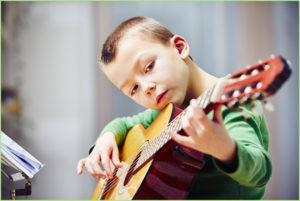 Учится мальчик играть на гитаре