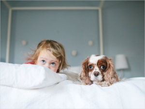Девочка с собакой на кровати