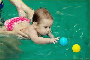 Девочку учат плавать