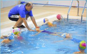 Тренер по плаванию учит девочек плавать