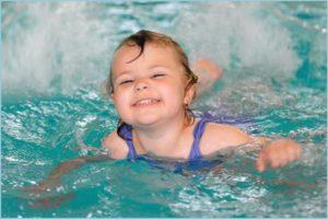 Девчушка плавает в бассейне