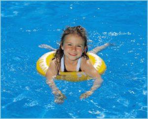 Девочка учится плавать с кругом
